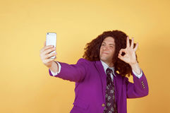 Den Caucasian mannen med afro bärande lilor passar ta en selfie Arkivbilder