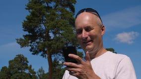 Den Caucasian mannen som bläddrar mobiltelefonen på gräsplan, sörjer bakgrund i sommarskog stock video