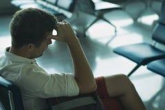 Den Caucasian mannen sover i vardagsrumområde på flygplatsen arkivbilder