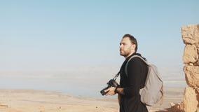 Den Caucasian mannen tycker om fantastisk panorama för det döda havet Den upphetsade fotografen står på bergöverkant med kameran  stock video