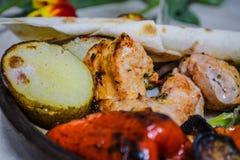 Den Caucasian maten med k?tt och exponeringsglas av r?tt vin Nationell georgisk matr?tt En kebab med gr?nsaker Tulpan royaltyfri foto