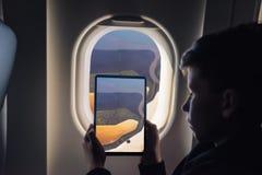 Den Caucasian pojken som använder minnestavlaPC:n för att ta bilden till och med nivåfönster, saltar damm i Don Edwards San Franc royaltyfri fotografi