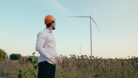 Den Caucasian teknikern i orange skyddande hjälm sätter på skyddsglasögon och ser vindgeneratorn av elektricitet i stock video