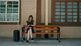 Den Caucasian unga damen väntar på drevet på stationsplattformen och läsning en bok lager videofilmer