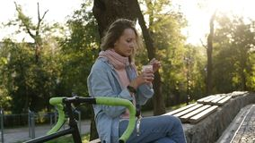 Den Caucasian unga flickan som dricker kaffe i en avslappnande dag parkerar in, på en bänk och att ha cykeln bredvid henne Morgon stock video