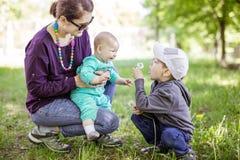 Den Caucasian unga kvinnan med behandla som ett barn dottern, och den förskole- sonen som tycker om härlig dag parkerar in arkivbild