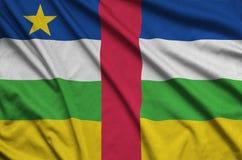 Den Centralafrikanska republiken flaggan visas på ett sporttorkduketyg med många veck Baner för sportlag arkivbild