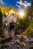 Den Cetatile grottan högg vid floden i romanian berg på solnedgången Arkivfoton