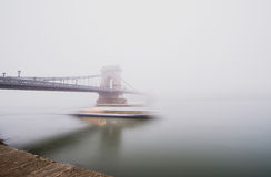 Den Chain bron över Donauen och ett fartyg, Budapest, Ungern, i dimma, aftonen tänder Fotografering för Bildbyråer
