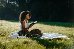 Den charmiga afrikanska flickan med naturligt smink och lockigt hår är avslappnande med boken under picknicken på det soligt Arkivbilder