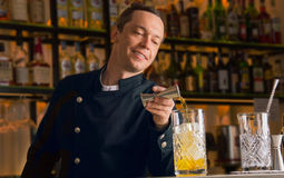 Den charmiga bartendern häller alkohol från en grej in i en mixin arkivbilder