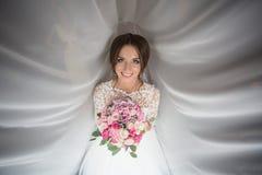 Den charmiga bruden håller en bröllopbukett Arkivbild