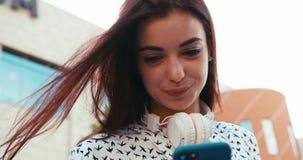 Den charmiga brunettdamen med nätt leende pratar på den utomhus- mobiltelefonen Upp ståenden längd i fot räknat 4k stock video