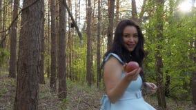 Den charmiga brunetten i blåttklänning går i skogen med äpplet i hand lager videofilmer