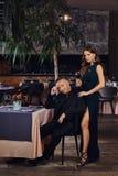 Den charmiga brunetten i en svart klänning står av hennes man som sitter på en tabell i en lyxig restaurang arkivfoto