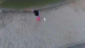 Den charmiga brunetten rymmer skor i händer och att cirkla runt om henne på stranden lager videofilmer