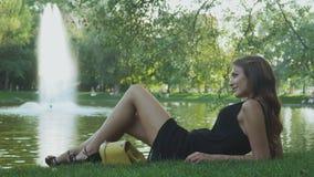 Den charmiga brunetten som lägger på greesgräs, är avslappnande nära dammet stock video