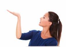Den charmiga damen i hållande rätt för blå skjorta gömma i handflatan upp Arkivbild