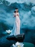 Den charmiga damen som står på ett enormt, vaggar i mitt av sjön royaltyfria foton