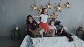 Den charmiga familjen har gyckel på julafton i sovrummet på sängen Flicka i en röd kjolbanhoppning på en säng med arkivfilmer