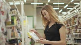 Den charmiga flickan köper förlängningskabel stock video