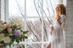 Den charmiga gravida flickan ser ut fönstret med en bukett av blommor Arkivfoton