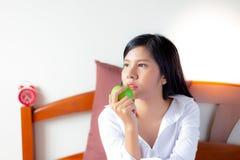 Den charmiga härliga kvinnan äter den gröna frukosten för äpplet i stället, därför att den nätta kvinnan önskar att banta Attrakt royaltyfri bild
