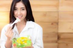 Den charmiga härliga kvinnan använder en gaffel för att få grönsak t royaltyfri bild