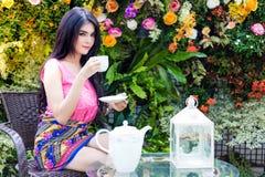 Den charmiga härliga kvinnan dricker kaffe eller te i eftermiddag arkivbilder
