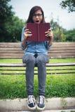 Den charmiga hipsterflickan förvånades som läser en roman medan sittien royaltyfria bilder