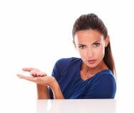 Den charmiga kvinnan i blått skjortainnehav gömma i handflatan upp Arkivfoto