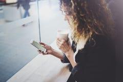 Den charmiga kvinnan med det härliga leendet som använder mobiltelefonen under, vilar i coffee shop suddighet bakgrund royaltyfri bild