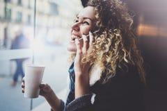 Den charmiga kvinnan med det härliga leendet som använder mobiltelefonen under, vilar i coffee shop suddighet bakgrund royaltyfri fotografi