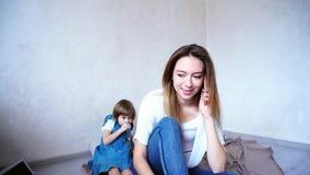 Den charmiga kvinnlign och barnet fostrar samtal på telefonen på bakgrund arkivbilder