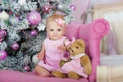 Den charmiga lilla flickan med blåa ögon som sitter i en rosa fåtöljnallebjörn på bakgrund, dekorerade julgranen Arkivbilder