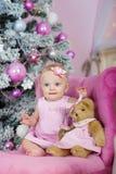 Den charmiga lilla flickan med blåa ögon som sitter i en rosa fåtöljnallebjörn på bakgrund, dekorerade julgranen Arkivbild