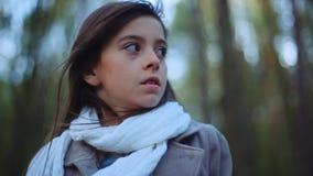 Den charmiga lilla flickan med en brunt skrämde ögon och långt brunetthår Ett skrämt barn står i mitt av lager videofilmer