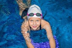 Den charmiga lilla flickan simmar i pölen Arkivfoton