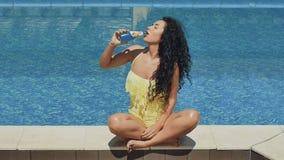 Den charmiga sexiga brunetten dricker en blå coctail med basilikafrö nära slår samman stock video