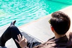 Den charmiga stiliga unga affärsmannen sitter nära simbassängen för royaltyfri fotografi