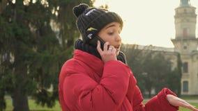 Den charmiga studenten i varm kläder talar på telefonen nära universitetsområde lager videofilmer