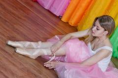 Den charmiga unga ballerina sätter på Pointe skor med band Arkivbilder