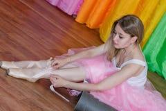 Den charmiga unga ballerina sätter på Pointe skor med band Royaltyfri Bild