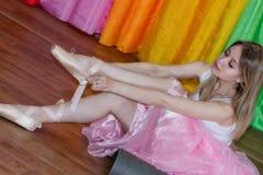 Den charmiga unga ballerina sätter på Pointe skor med band Fotografering för Bildbyråer