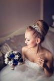 Den charmiga unga blonda bruden i en vit snör åt klänningen sitter på sängen i inre av huset, i profil Royaltyfri Foto