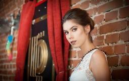 Den charmiga unga brunettkvinnan i vit snör åt blusen nära en vägg för röd tegelsten Attraktivt ursnyggt dagdrömma för ung kvinna Arkivfoton