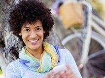 Den charmiga unga kvinnan i sommar parkerar med mobilen Arkivbilder
