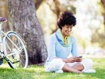 Den charmiga unga kvinnan i sommar parkerar med mobilen Royaltyfri Foto