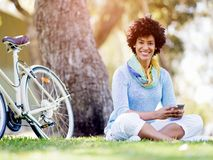 Den charmiga unga kvinnan i sommar parkerar med mobilen Royaltyfri Bild