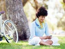 Den charmiga unga kvinnan i sommar parkerar med mobilen arkivfoto